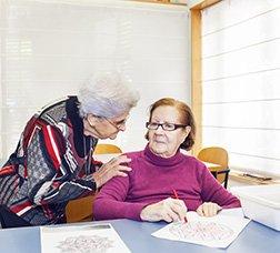 Dues usuàries d'un centre de dia parlant mentre una fa una activitat d'escriptura