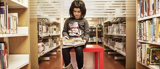 Girl sitting on a table reading a book in a library corridor