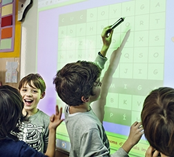 Niños y niñas en clase con una pizarra digital