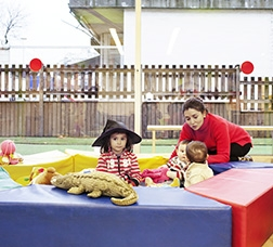 Group of children playing with soft toys and an adult woman