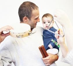 Nadó en els braços del seu pare mentre fa música amb una pandereta i la mare, amb un triangle