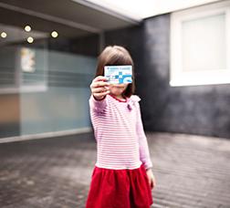 Nena amb la targeta sanitària a la mà i ensenyant-la