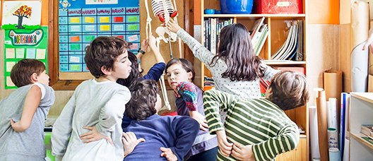 Students playing with a skeleton in a classroom.
