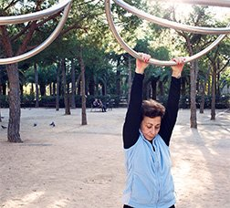 Woman doing stretching exercises at a training circuit.