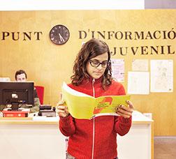 Chica leyendo un díptico en un punto de información juvenil