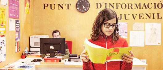Noia llegint un díptic en un punt d'informació juvenil