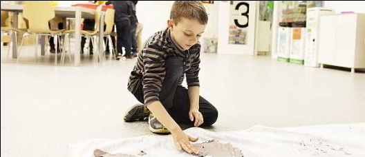 Boy doing a workshop with mud on the ground
