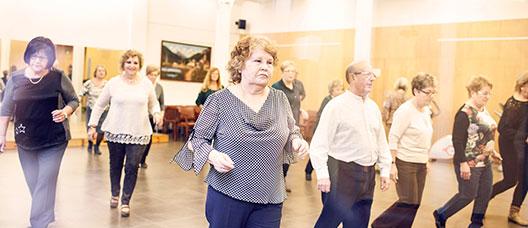 Grup de persones assistint a una classe de ball en un casal