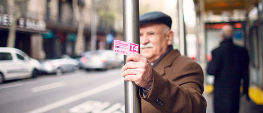 Man waiting for the bus at a bus stop, holding the Pink Card in his hand