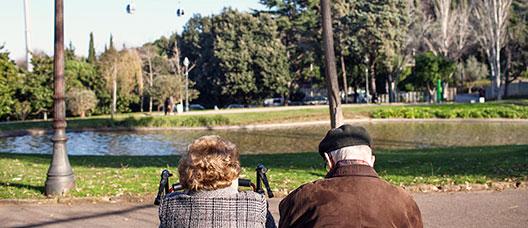 Matrimoni assegut en un banc d'un parc