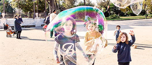 Group of children running after a soap bubble in the Parc de la Ciutadella