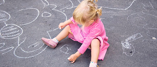 Girl sitting on the ground drawing with a chalk on the pavement