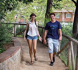 Una chica y un chico pasean por un parque