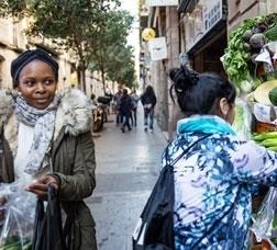 Dues noies compren verdures a l'exterior d'una botiga.