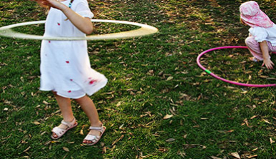 Young children playing with hula-hoops in a park
