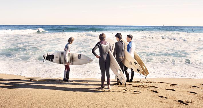 Grupo de surfistas a la orilla del agua con la tabla de surf bajo el brazo