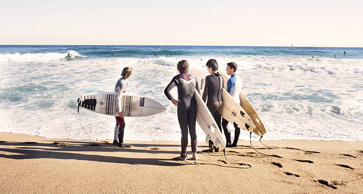 Group of surfers at the shore with surfboards under their arms