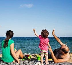 Una família que està asseguda a la platja saluda un avió