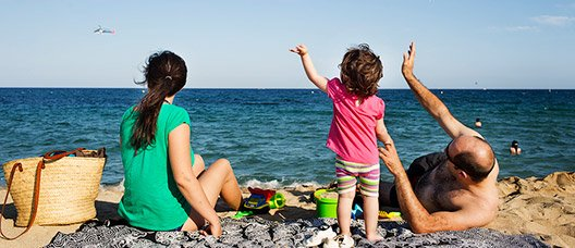 A family wave at an aeroplane as they sit on the beach