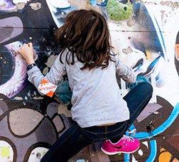 Unos niños practican escalada en un rocódromo