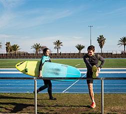 Una mujer camina con una tabla de surf y un hombre realiza estiramientos en la pista de atletismo del Centre Esportiu Municipal La Mar Bella
