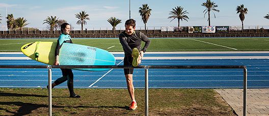 A woman walks with a surfboard and a man warms up at the athletics track at the Mar Bella municipal sports centre