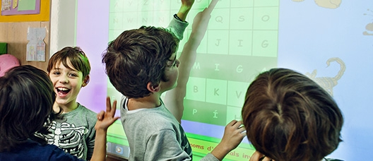 Nens i nenes a classe amb una pissarra digital