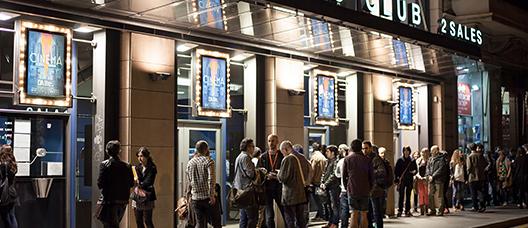 Personas haciendo cola en la entrada de un cine