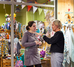 Una comerciante conversa con una mujer en la puerta de una tienda de ropa infantil.