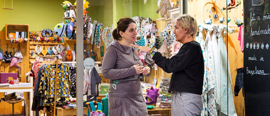 A shopkeeper speaking to a woman by the door of a children's clothes shop.