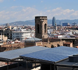 Panorámica de Barcelona con unas placas fotovoltaicas en primer plano