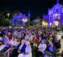 Públic assegut escoltant un concert als jardins del Recinte Modernista de Sant Pau.