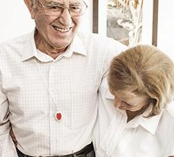 Matrimonio abrazado y riendo con el botón de la teleasistencia colgado en el cuello