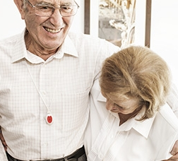 Couple embracing and laughing with the teleassistance button hung around their necks