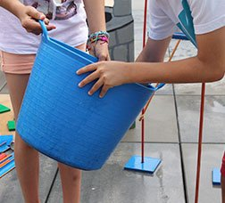 Children with a bucket of water preparing an outside installation.