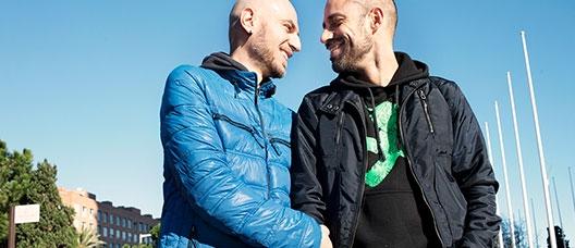 Pareja de homosexuales cogidos de la mano y sonriendo mientras se miran