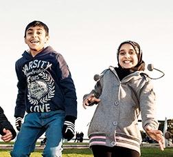 Menores de diferentes nacionalidades saltando y riendo en un parque