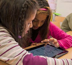 Two girls in a classroom practising calligraphy on a touch-screen tablet