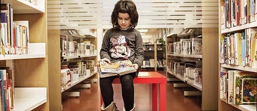 Niña sentada sobre una mesa lee un libro en el pasillo de una biblioteca