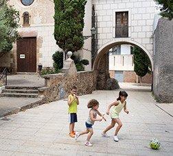 Dos niñas y un niño juegan a pelota en una calle peatonal