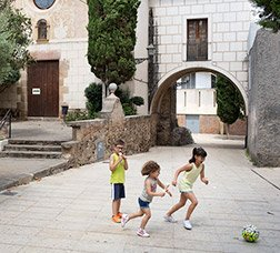 Two girls and a boy play with a ball in a pedestrianised street