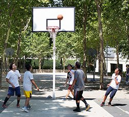 A group of youngsters play basketball in a park