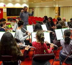 Ensayo de un grupo de niñas y niños que tocan instrumentos de viento