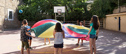 Un grup de nenes i nens juguen al pati d'una escola
