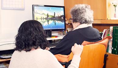 Una chica joven ayuda a una mujer mayor a utilizar un ordenador.