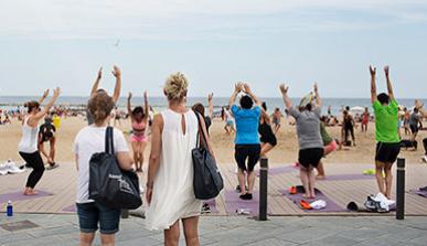 Dos mujeres miran a un grupo de personas que practica yoga en la playa