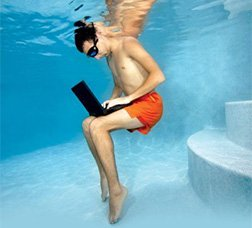 A man writing on a laptop under water in a swimming pool