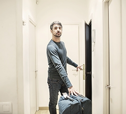 Man in an apartment with a suitcase