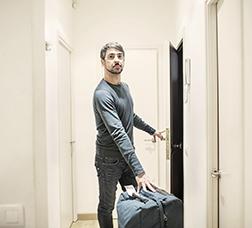 Home dins d'un pis amb una maleta