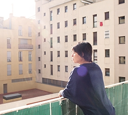 Dona mirant pel balcó d'un pis de protecció oficial